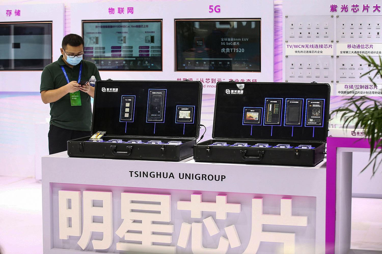 """紫光集团被视为实现""""中国芯""""的龙头。这家中国最大晶片制造商上星期债券价格突然暴跌。集团周一表示,因公司流动资金紧张,令规模达13亿元人民币、票息5.6%的私募债不能按期足额支付。图为,2020年8月26日,在南京举行2020年世界半导体会议上展示紫光集团的芯片。(法新社)"""