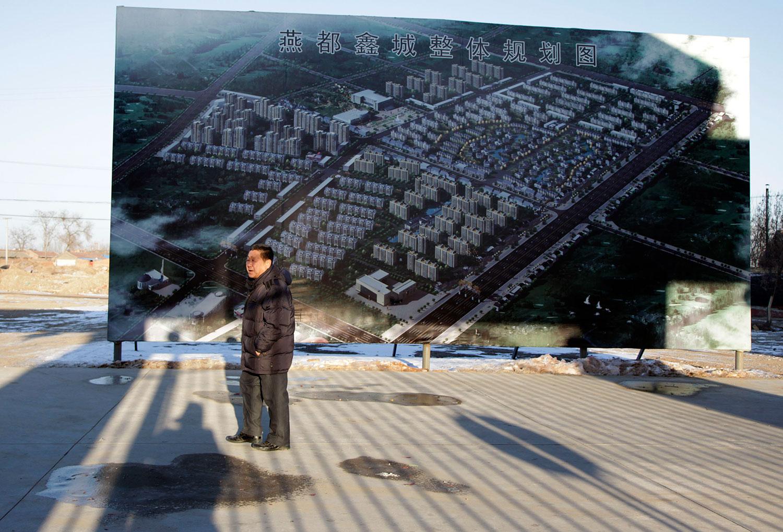资料图片:2011 年 2 月 11 日,曾经是农民的李惠山(音译)在他的新公寓外散步,附近的一块板子上挂着一幅画,画面显示河北省安平镇为农民搬迁而建造的公寓楼。 (美联社)