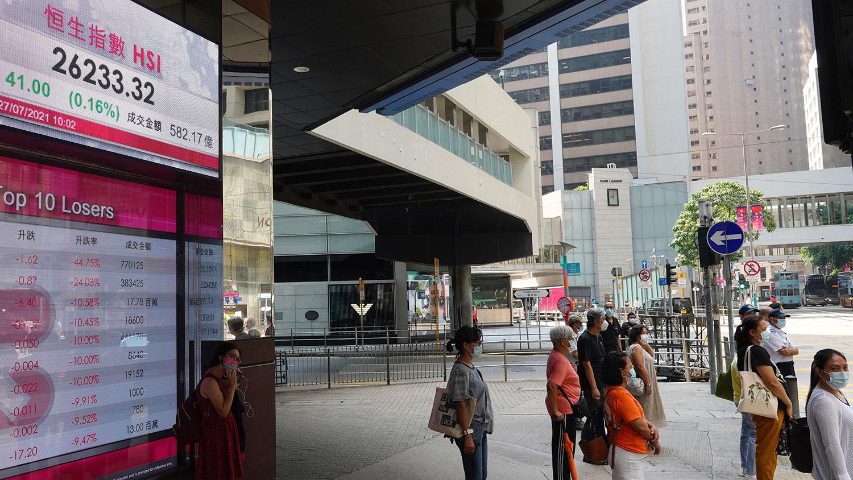 2021 年 7 月 27 日,人們站在香港聯交所顯示香港股票指數的銀行電子板前。 (美聯社)