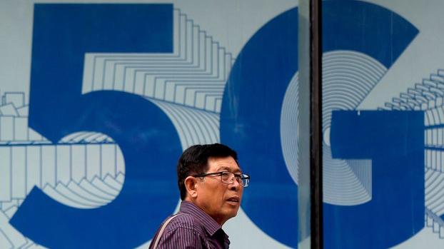 资料图片:2019年6月6日,一名男子走过在北京购物区展出的5G网络广告。(美联社)
