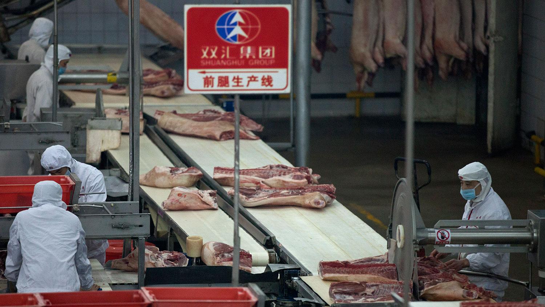 目前中国的生猪调配范围普遍在300公里以内,猪肉的价格受地域影响较大,不少地区的猪肉零售价格涨幅接近30%。图为,河南双汇集团有限公司,员工在猪肉加工厂工作。(AFP)
