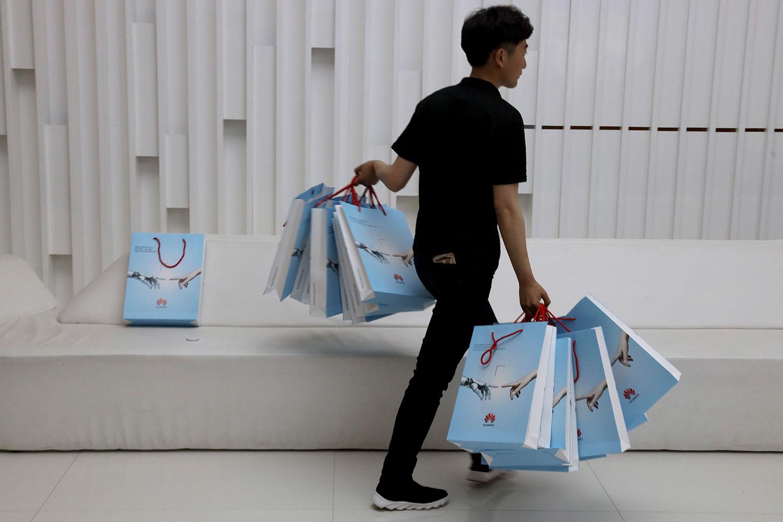 中美就贸易谈判陷于僵局,而苹果公司作为其中一家最具知名度的美国品牌企业,很有可能成为报复对象。图为2019年5月15日,北京华为展后,一公司人员双手拿着华为新产品包。(资料图/美联社)