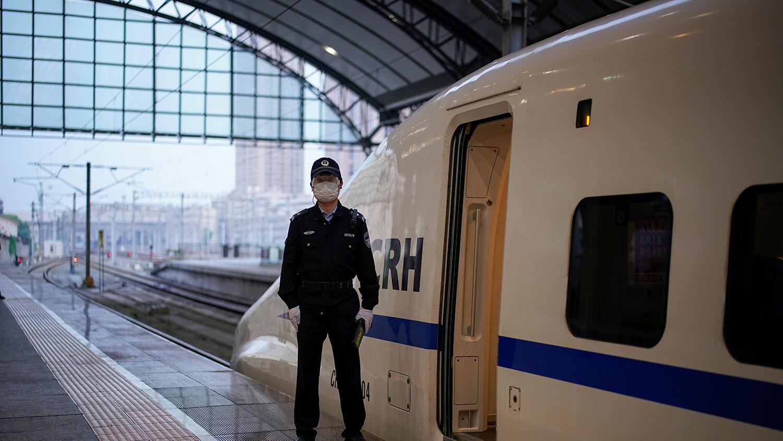 2020年4月8日,警察站在高速火车的旁边,这是两个月以来第一趟从武汉汉口火车站出发的火车,因冠状病毒病(COVID-19)爆发的中心城市的出行限制在武汉市通过公路,铁路和飞机离开城市。(路透社图片)