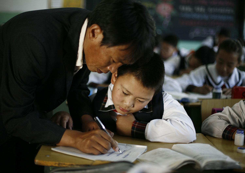 图为一名老师在课堂上帮助学生。(美联社)