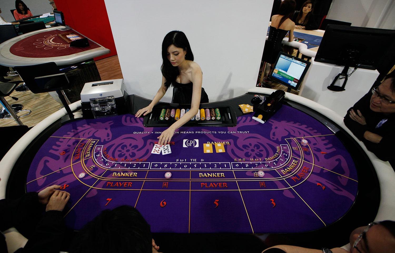在疫情持续下,中国中央严打资金外流,使澳门博彩业面临空前危机。图为服务员在澳门亚洲博彩博览会上的百家乐游戏桌上演示了百家乐游戏。(AP)