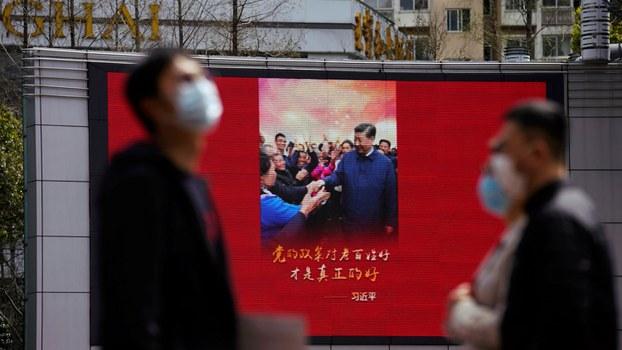 中国国内无症状感染者的频繁出现已引起民众高度恐慌。图为上海戴口罩的行人走过一幅显示中国国家主席习近平图像的屏幕。(路透社)