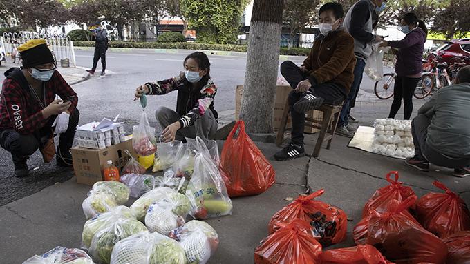 """疫情高峰之后的武汉街头。武汉政府在5月6日召开的动员大会上鼓励公务员与企业家""""打交道、交朋友""""。(美联社)"""