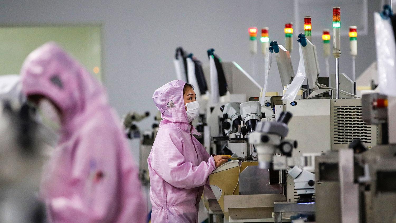 2020 年 2 月 16 日,员工戴着口罩和防护服在江苏省泗洪市的一条智能芯片生产线上工作。(法新社)