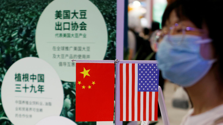2021 年 9 月 4 日,北京舉行的 2021 年中國國際服務貿易交易會(CIFTIS)期間,一名婦女走過美國大豆出口委員會展位上展示的中國和美國國旗。(路透社)
