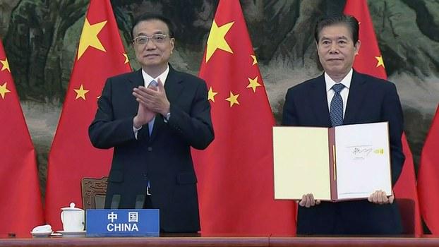 2020年11月15日,中国总理李克强(左)和中国商务部长钟山在区域全面经济合作伙伴关系(RCEP)签字仪式上签署贸易协定。(法新社)