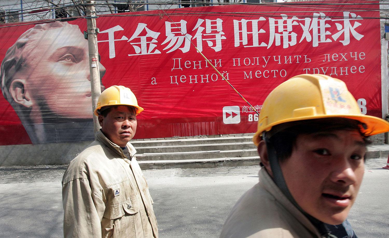 资料图片:2006年3月19日,建筑工人在北京俄罗斯城雅宝路的中文和俄文广告牌走过。(法新社)