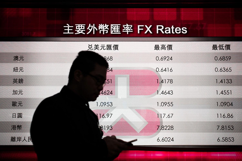 一名男子在显示香港汇率的电子板前查看手机。(法新社图片)