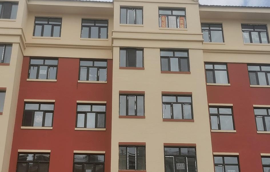雙鴨山市康安嘉園一些房屋窗戶上都貼着售房信息,其中包括50平方米住房,售價1.2萬元人民幣。(證券時報圖片)