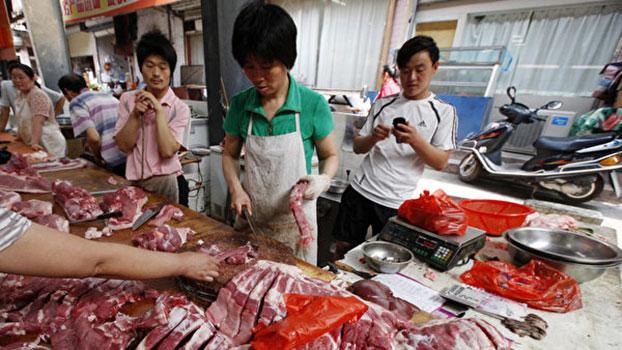 貿易戰影響中國股市、樓市等消費品領域,其中末端消費者受到的傷害最大,民衆基本生活用品近期也出現價格急升的現象,蔬菜、水果、肉類漲價的幅度都非常大。圖爲安徽淮北某市場,市民們在選購豬肉。(AFP)