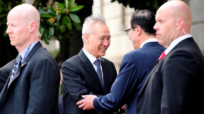 2019年5月9日,美国贸易代表办公室外,中国副总理刘鹤与美国财政部长姆努钦握手。(路透社)
