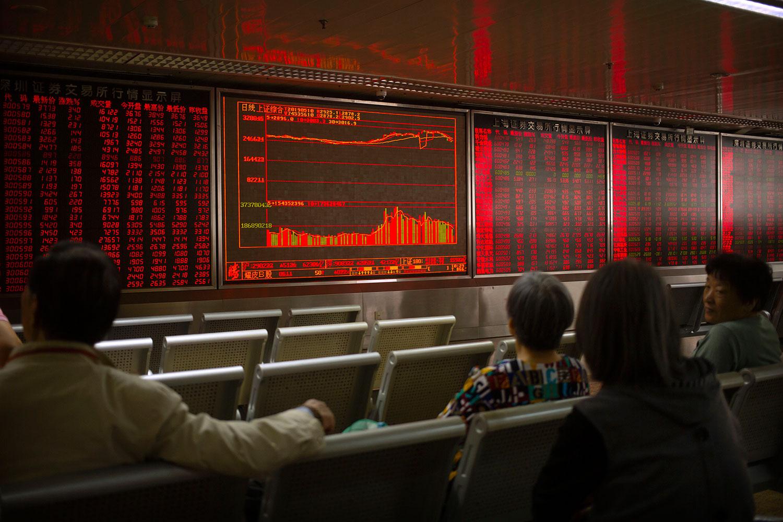 美国宣布加征关税后,中国和香港的股票市场不跌反升。图为2019年5月10日,市民在北京一经纪公司观看股票。(美联社)