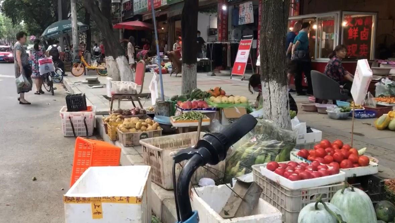 """成都摊贩获城管鼓励,""""违规""""街头摆卖。(志愿者提供/记者乔龙)"""