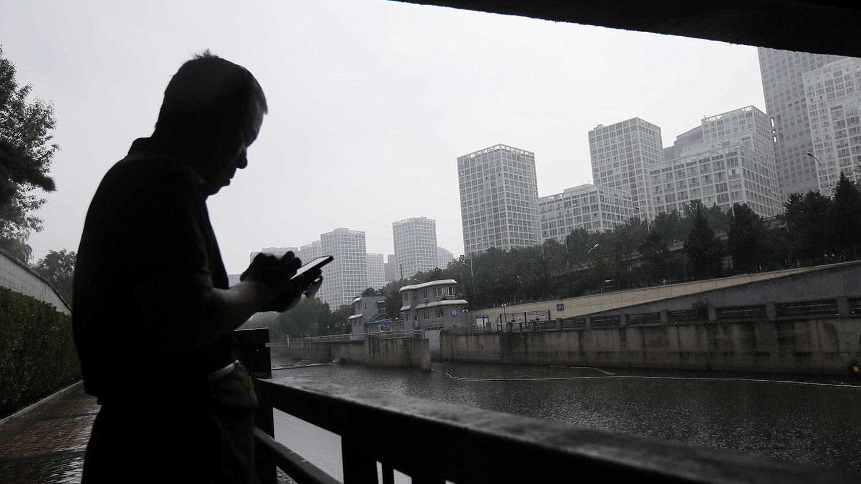學者認爲中國經濟模式已走到盡頭。圖爲,北京商務中心區 (CBD),一名男子在河邊使用手機。(REUTERS)