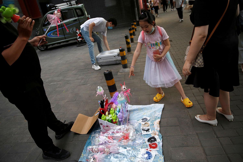 图为在北京街头小摊上出售玩具。(路透社)