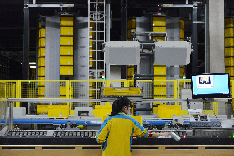 """国进民退之下民企规模逐渐萎缩。图为,2019年11月11日,中国江苏省南京市的""""双十一""""在线购物节,一名员工在苏宁物流基地工作。(路透社)"""