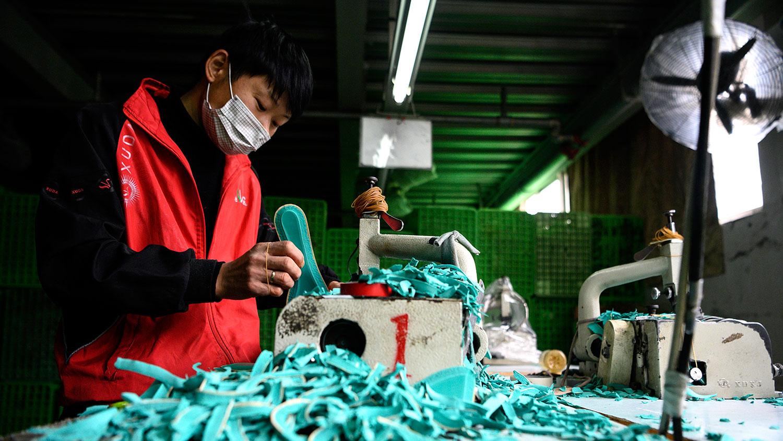 50%为荣枯线,中国PMI在50以下意味着制造业活动正在萎缩。图为,2020年2月27日,工人在浙江温州一家鞋业有限公司的厂房制造鞋垫。(法新社)