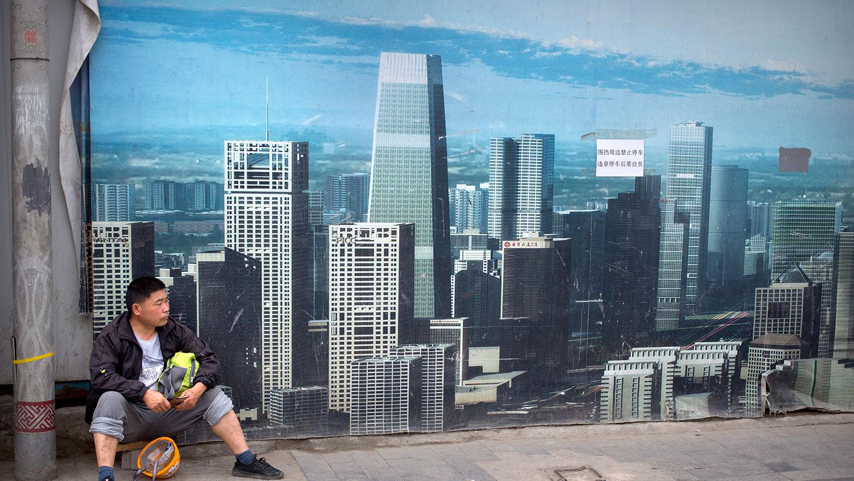 受到美中贸易战影响,去年以来,中国出口贸易、房地产、制造业及全国用电量等领域均出现明显衰退趋势。图为2019年5月16日,一名工人坐在北京某建筑工地广告牌前。(资料图/美联社)