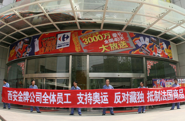 """资料图片:2008年4月17日,当地公司的员工在陕西省西安家乐福超市外面举着""""支持奥运会,反对西藏独立,抵制法国商品""""的横幅。(路透社)"""