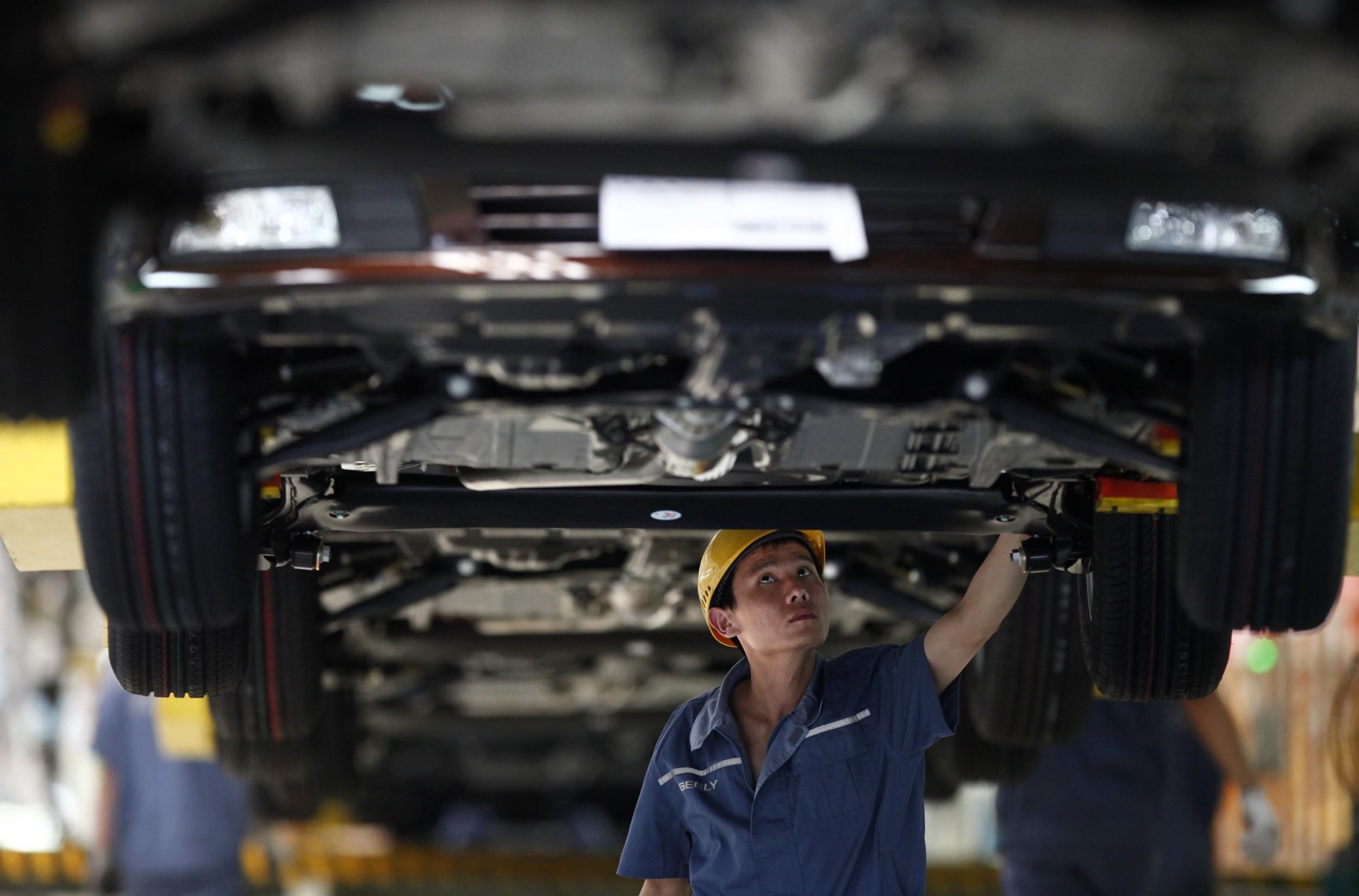 2012年6月21日,一名员工在浙江吉利汽车公司装配线上工作。(路透社)
