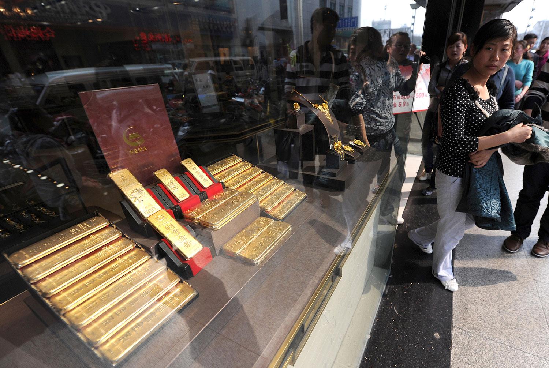 在过去20年,中国民众对黄金首饰及投资性金条和金币的需求量增长两倍以上。其中黄金储备近2000吨。图为安徽省一家黄金店展示黄金条。(资料图/法新社)