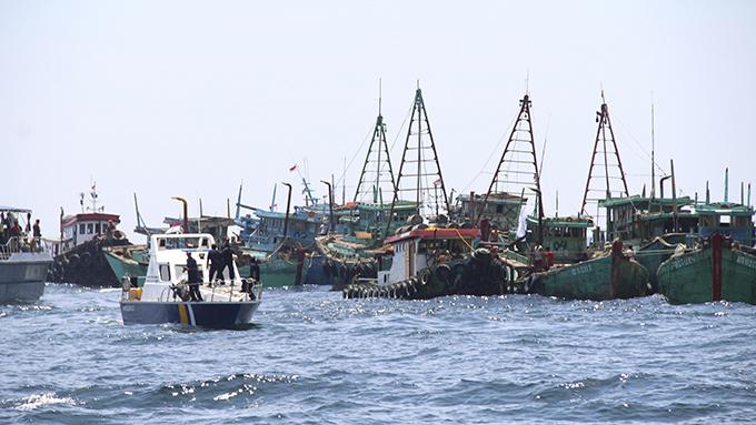 资料图片:2019年5月4日,印尼海洋渔业部的一艘巡逻艇对因非法捕鱼而被扣留的外国渔船进行检查。(美联社)