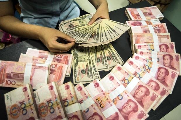 银行工作人员在数点人民币和美金。(法新社)