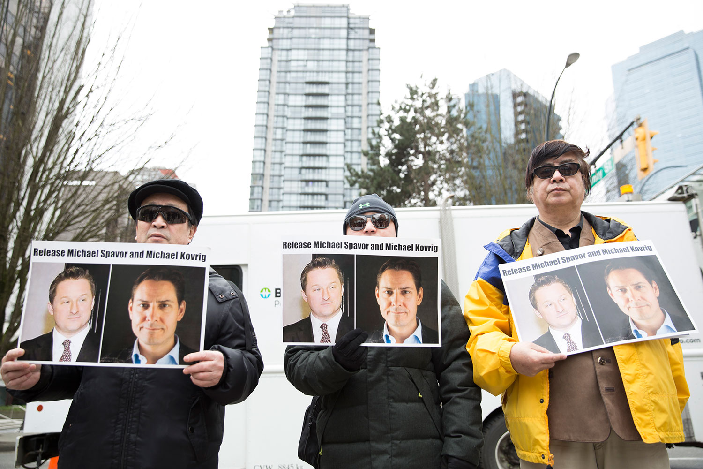 2019年3月6日,中国华为高管孟晚舟在加拿大温哥华出庭。法庭外民众举着被中国逮捕的加拿大公民康明凯和斯帕弗的照片,要求中国放人。(路透社)