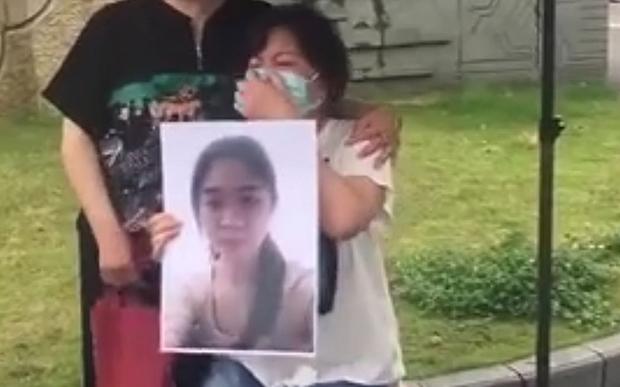学生家长手举宁波工程学院外教杀人事件遇难者的照片(微博截图)