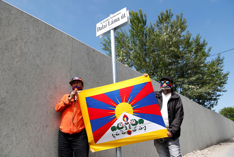"""2021年6月2日,民众在计划兴建中国复旦大学布达佩斯分校的校址附近,一条名为"""" 达赖喇嘛道 """"(a Dalai Láma út)的路牌下手举雪山狮子旗。(路透社)"""