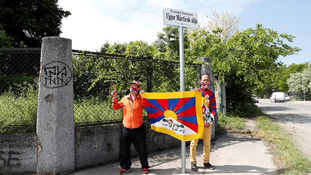 """民众2021年6月2日在计划兴建中国复旦大学布达佩斯分校的校址前被命名为""""维吾尔烈士径""""的路牌下手举雪山狮子旗(路透社)"""