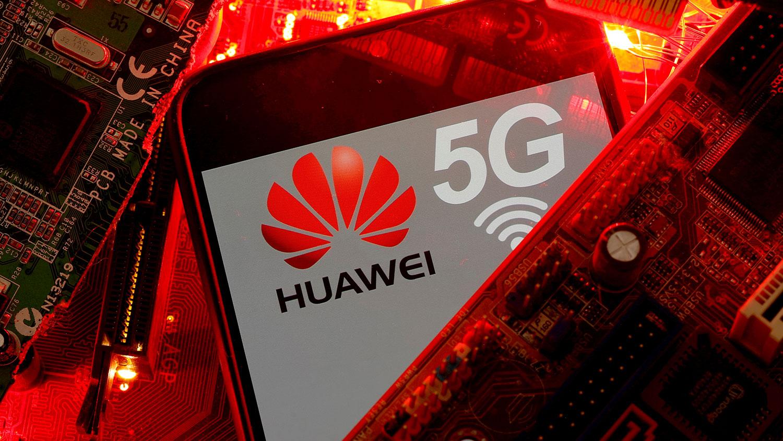资料图片:PC 主板上带有华为和 5G 网络标志的智能手机。(路透社)