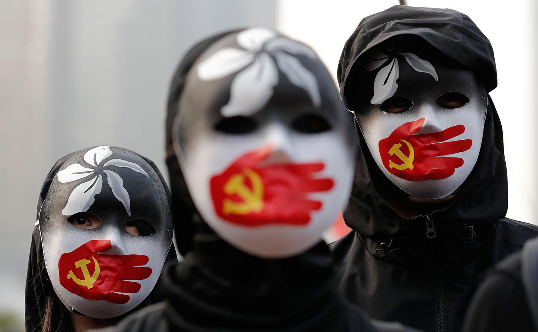 圖爲,2019年12月22日,身着黑衣蒙面示威者在香港中心地帶集會,聲援維吾爾族及香港人權自由。 (美聯社)