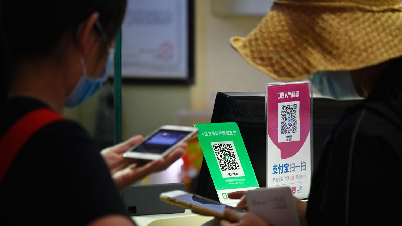 图为,2020年9月19日,北京一家食品商店中微信支付和支付宝的QR码。(AFP)