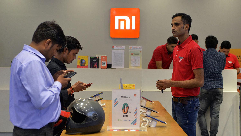 数据显示,小米是印度最受欢迎的手机品牌,市占率曾连续10年冠军。图为,2019年8月20日,客户在印度古尔冈小米商店检查小米智能手机。(法新社图片)