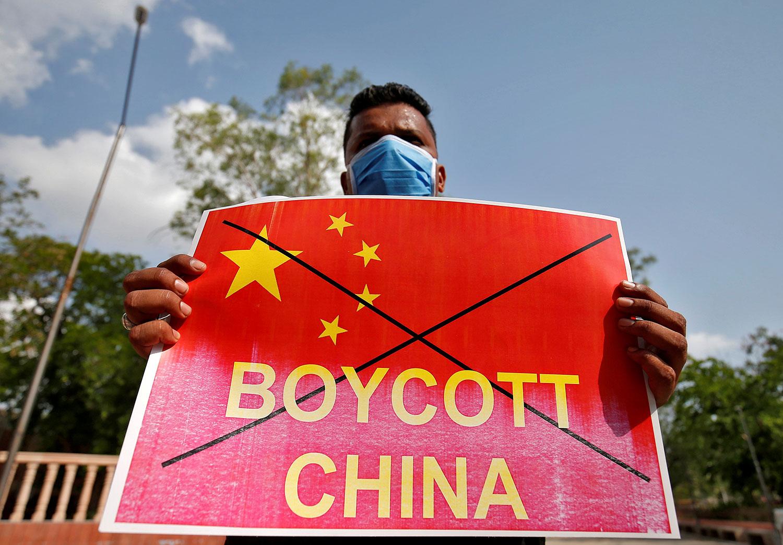 """2020年6月18日,一名印度全国学生联合会(NSUI)成员在印度艾哈迈达巴德的一场反华抗议活动中举着写有""""抑制中国""""的标语牌。(路透社)"""