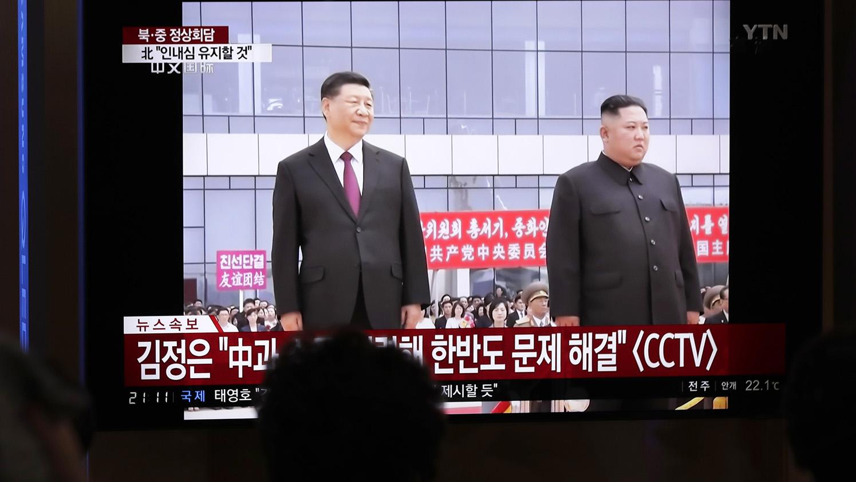 韩国民众在电视上观看金正恩接待习近平访问朝鲜的画面。(美联社)