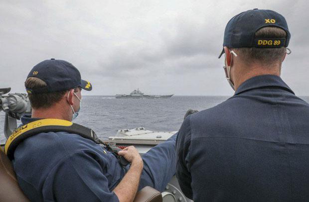 """2021年4月4日美军发布神盾驱逐舰""""马斯廷号""""舰长跷脚远看中国辽宁号的照片。(美国海军网)"""