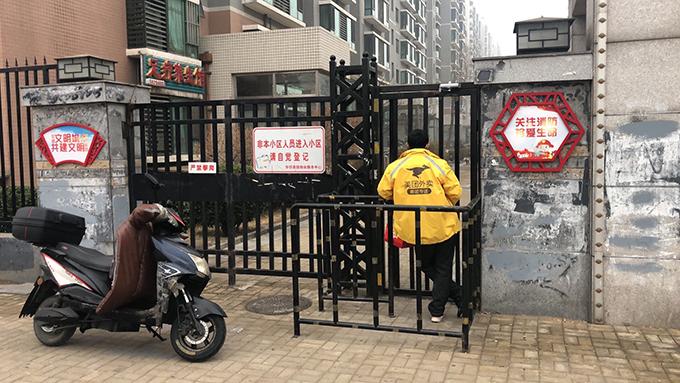 为避免新冠病毒感染,中国的许多居民小区对外关闭。图为北京一个小区外等待顾客接收定货的外卖。(Photo by Dylan Wang)