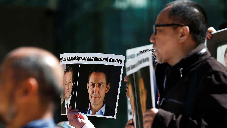 2019年5月8日中國華爲高管孟晚舟在加拿大溫哥華出庭。法庭外民衆舉着被中國逮捕的加拿大公民康明凱和斯帕弗的照片,要求中國放人。(路透社)
