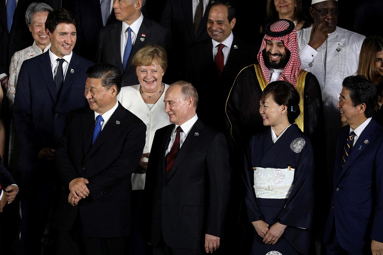 2019年6月28日在大阪举行的G20峰会期间,,(LtoR)加拿大总理特鲁多,中国国家主席习近平,德国总理默克尔,俄罗斯总统普京,日本首相安倍晋三和他的妻子阿基以及沙特王储穆罕默德·本·萨勒曼合影。(法新社)