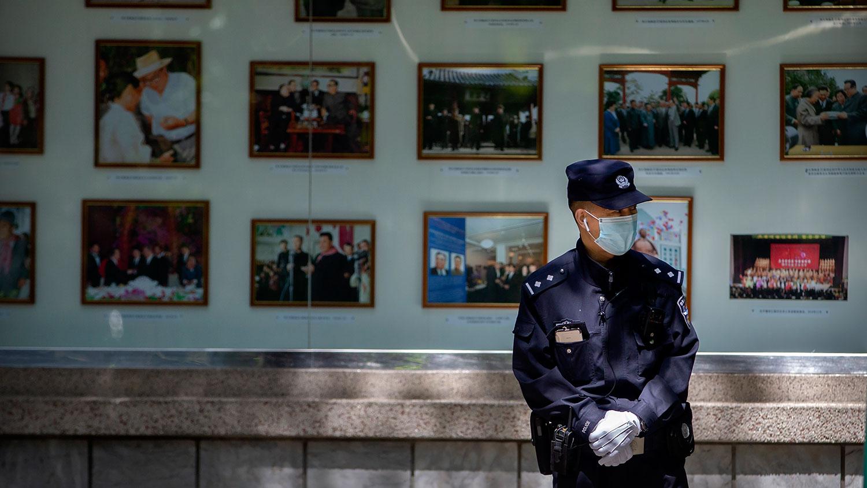 2020年4月21日,一名中国警察站在朝鲜驻北京大使馆外的朝鲜领导人照片展示前。(美联社)