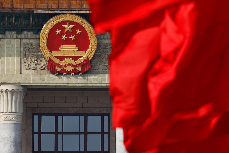 中国人大常通过《反外国制裁法》,学者警告北京别高估自己实力。图为,北京人民大会堂外的中国国徽附近,红旗飘扬。 (美联社图片)