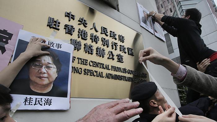 资料图片:2016年2月29日,香港民众把桂民海的照片贴在中联办的牌子上。(美联社)