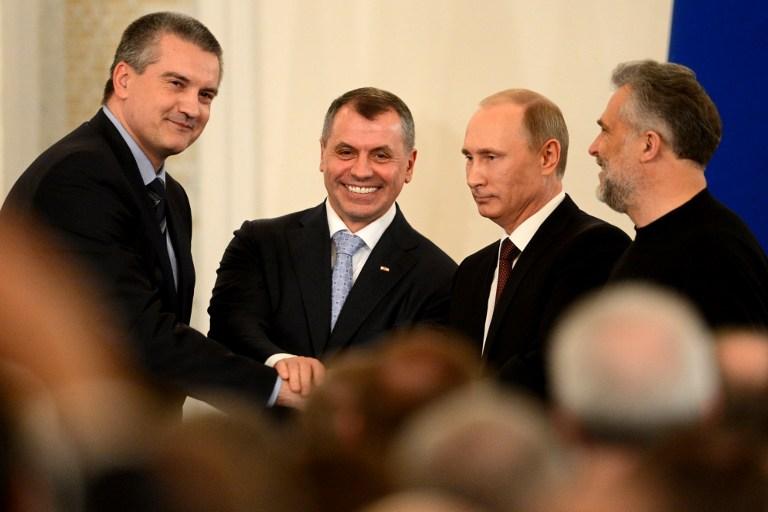 2014年3月18日,在莫斯科的克里姆林宫内,俄罗斯总统普京(右二)与来访的克里米亚代表团共同签署了克里米亚和直辖市塞瓦斯托波尔加入俄罗斯的协议。(法新社)