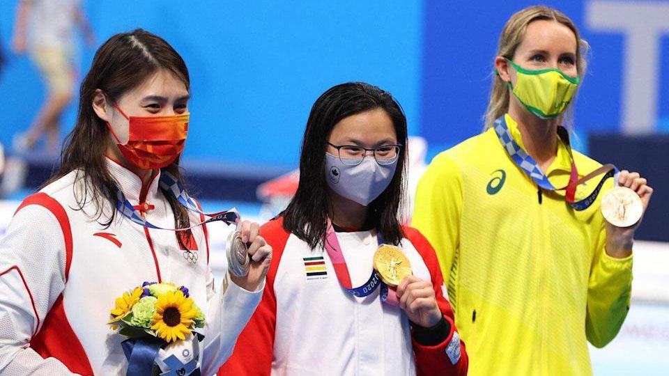 玛姬(中)在100米蝶泳项目中击败中国选手张雨霏(左)。 (Public Domain)